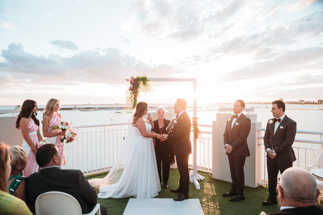 sun sets in the background during the wedding ceremony