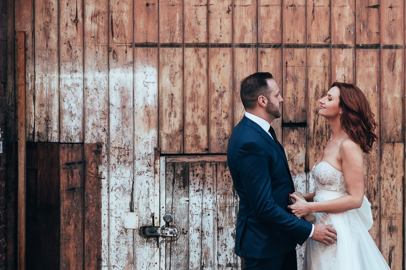 the couple looks at each other against a wooden wall, post wedding photos
